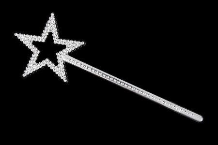 Baguette magique argentée scintillante avec étoile sur fond noir.