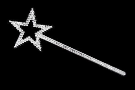 Glittery silver magic wand with star on black background.