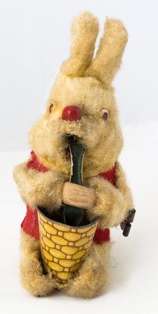Vintage wind-up bunny eating vegetables from basket. Vertical.