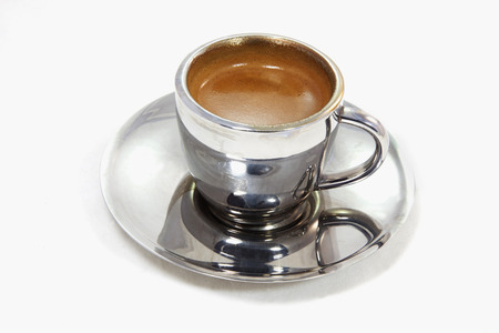 Shiny steel cup and saucer of espresso. Isolated.