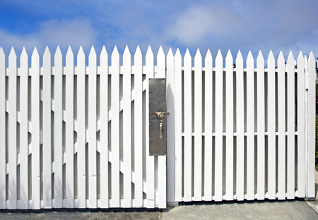Elegant and simple white wood picket fence and gate under blue sky.