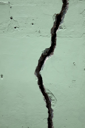 Fissure crack in green concrete wall. Vertical. Stok Fotoğraf