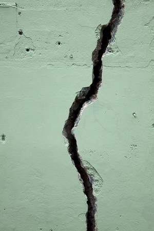 Fissure crack in green concrete wall. Vertical. Banco de Imagens