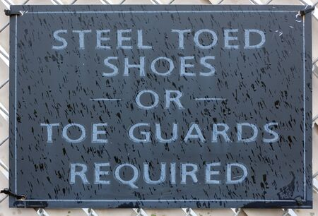 Rain splattered construction site sign requiring STEEL TOED SHOES OR TOE GUARDS.