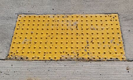 Yellow bumpy tactile sidewalk ramp pad alerting pedestrians they are approaching a sidewalk.