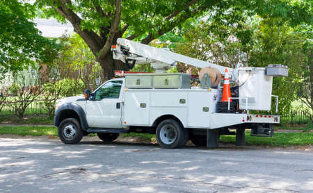 Front and side view of parked communication utility trucks in residential neighborhood. Horizontal. Stock Photo