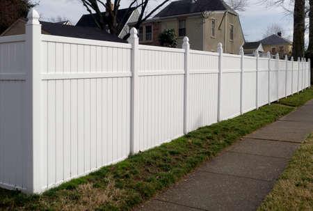New white vinyl resin fence in residential neighborhood.