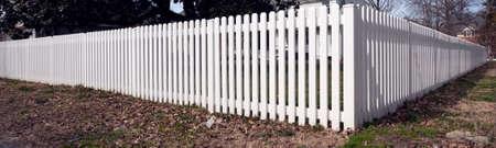 White plastic picket fence on corner lot. 写真素材