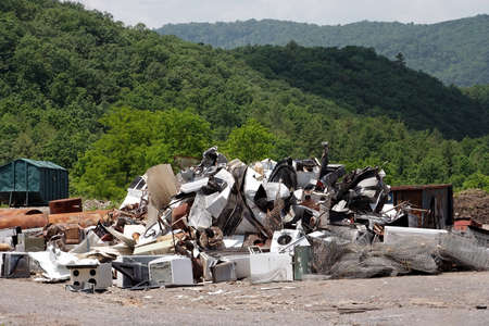 Garbage and rubbish with mountain landscape in background. Rural trash dump or landfill site. Pollution concept.