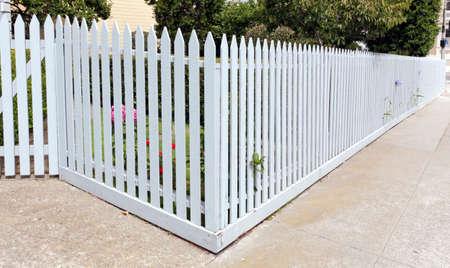 White picket fence on corner lot with sidewalk.