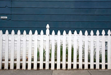 Older white picket fence with blue wall in background.