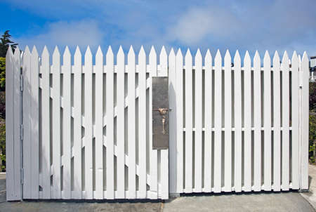 White picket fence gate with blue sky.
