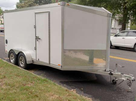White utility trailer parked on neighborhood street.