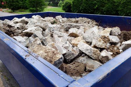 Dumpster filled with sidewalk concrete debris in neighborhood setting.