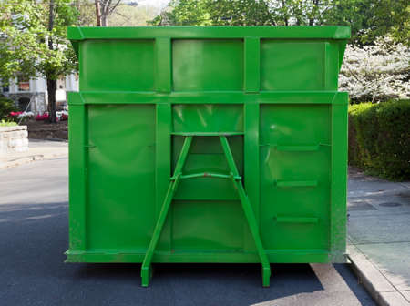 Newly painted green industrial dumpster container parked on neighborhood street. Isolated.