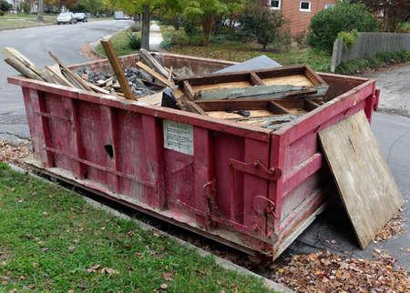 Filled red industrial construction dumpster curbside in residential neighborhood. Horizontal. 版權商用圖片