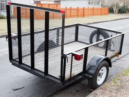 Empty two-wheel trailer with wire mesh sides parked on residential neighborhood street.