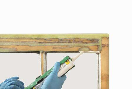Close up of a person applying dry seal to restored sash windows. Sash window restoration. Reklamní fotografie