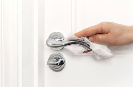 A person cleaning door handle to prevent the spread of germs, bacteria and corona virus.