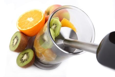 licuadora: Las frutas frescas se mezclan con la batidora de mano Foto de archivo