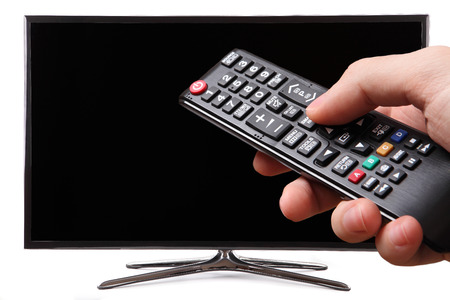 Mano que sostiene el control remoto del televisor con una televisión inteligente en segundo plano Foto de archivo