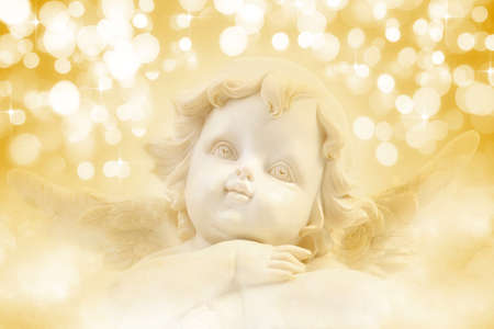 Christmas Angel a background of golden holiday lights photo