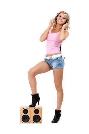 musica electronica: Chica joven hermosa con los auriculares y los altavoces aislado en blanco