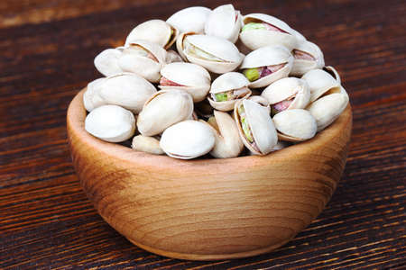 Pistachios in wooden bowl over wooden background(selective focus). Stock Photo
