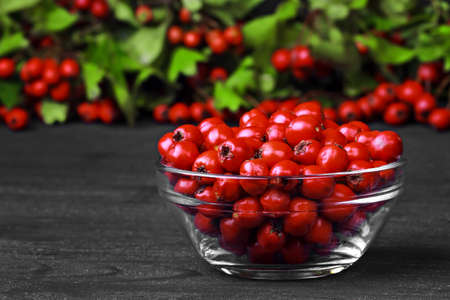 decorate: Hawthorn berries (crataegus) in glass bowl on a old black wooden table (selective focus).