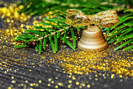 desk: Golden bell and pine branches on black wooden background (selective focus).Use it for different holiday greeting cards -  Advent, Christmas or New Year Stock Photo