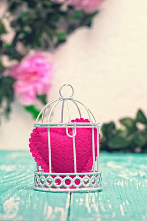 Still life romantic background with heart shaped ornament in decorative bird cage on teal wooden planks and pink flowers on wall in the background (selective focus).