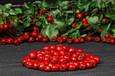 Hawthorn berries (crataegus) on black wooden table (selective focus).