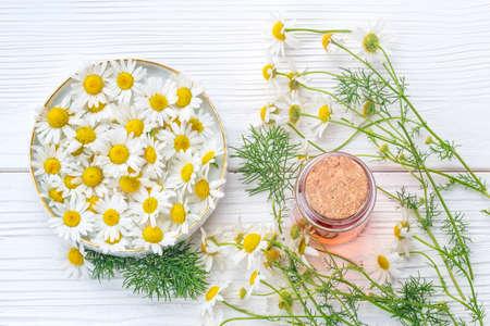 Aceite esencial en botella de vidrio con flores de manzanilla frescas, vista superior. Concepto de medicina alternativa en una mesa de madera blanca (enfoque selectivo).
