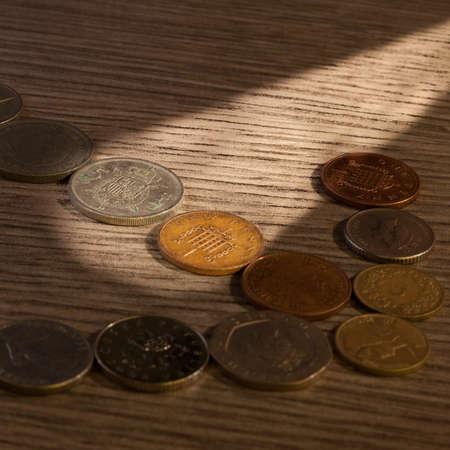 monete antiche: Vecchie monete fascio di luce. Penny e Peseta Archivio Fotografico