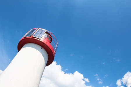 sea mark: Lighthouse Photovoltaic Sky . Sea Mark at the harbor with blue sky with clouds in background