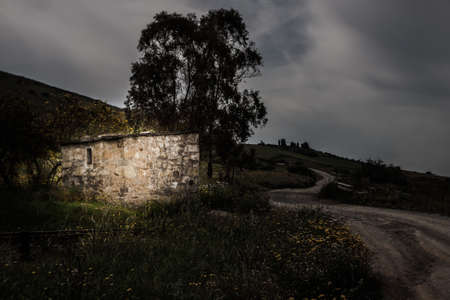 sunup: Nightime stone house campaign. Stone house in an old grade crossing Stock Photo