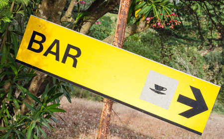 where to eat: Yellow signboard bar. Sign that indicate bar and place where its possible drink and eat. Symbol of cup of coffee Stock Photo