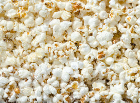 eating popcorn: Hundreds popcorns background. Popcorns behind the glass of popcorn machine