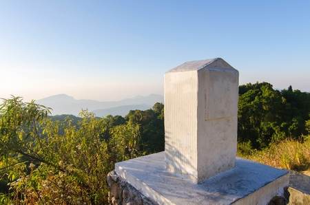 kilometer stone or mile stone with blue sky and trees at mountain. Stock Photo