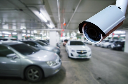 cctv security camera on blurred background of indoor car park, security technology concept. Stockfoto