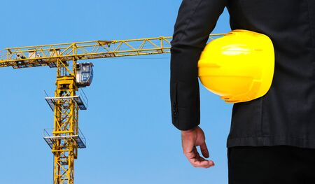 industrial machinery: businessman hold in hand yellow safety helmet  business industrial concept on yellow construction tower crane with blue sky background.