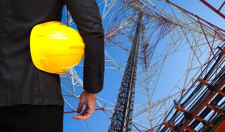 receiver: businessman in suite with yellow safety helmet with telecommunication tower with blue sky background, business technology industrial concept. Stock Photo
