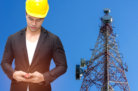 smart construction manager in suite with walkie-talkie or two way radio in hand and yellow safety helmet with telecommunication tower blue sky background, technology, business and industrial concept. Stock Photo