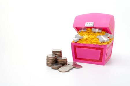 booty: Piggy bank or Treasure Chest shaped money box with coins on white background, in saving money concept, copy space Stock Photo