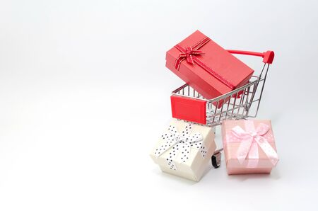 Mini supermarket shopping cart with mini colorful gift box on white background Stockfoto