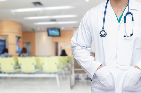 smart doctor with a stethoscope around his neck with blurred image of people waiting at hospital background, healthcare medical technology concept, copy space, color effect tone