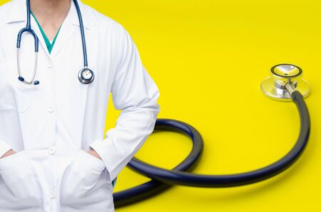 smart doctor with a stethoscope around his neck with stethoscope on yellow background, heart health care and medical technology concept, selective focus, copy space Stock Photo