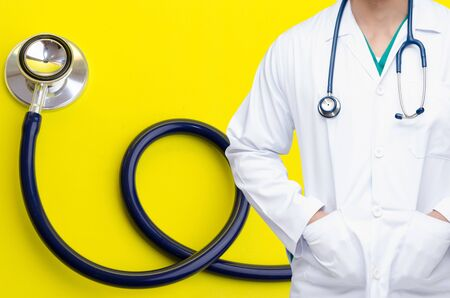 smart doctor with a stethoscope around his neck with stethoscope on yellow background, heart health care and medical technology concept, selective focus.