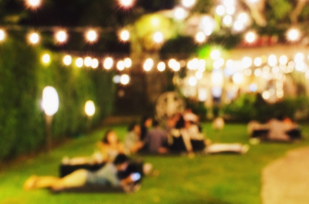 abstract urban night light bokeh of night music festival with people in garden, light blurred background, vintage color tone, festival holiday light background concept