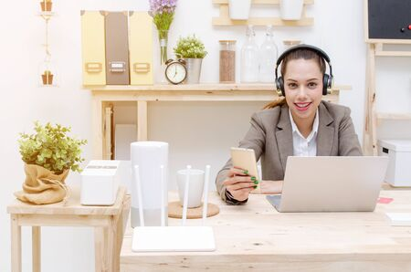 asian young business customer service woman smiling in headset working with laptop, business woman listening music with headphones in office, business technology lifestyle concept, soft focus